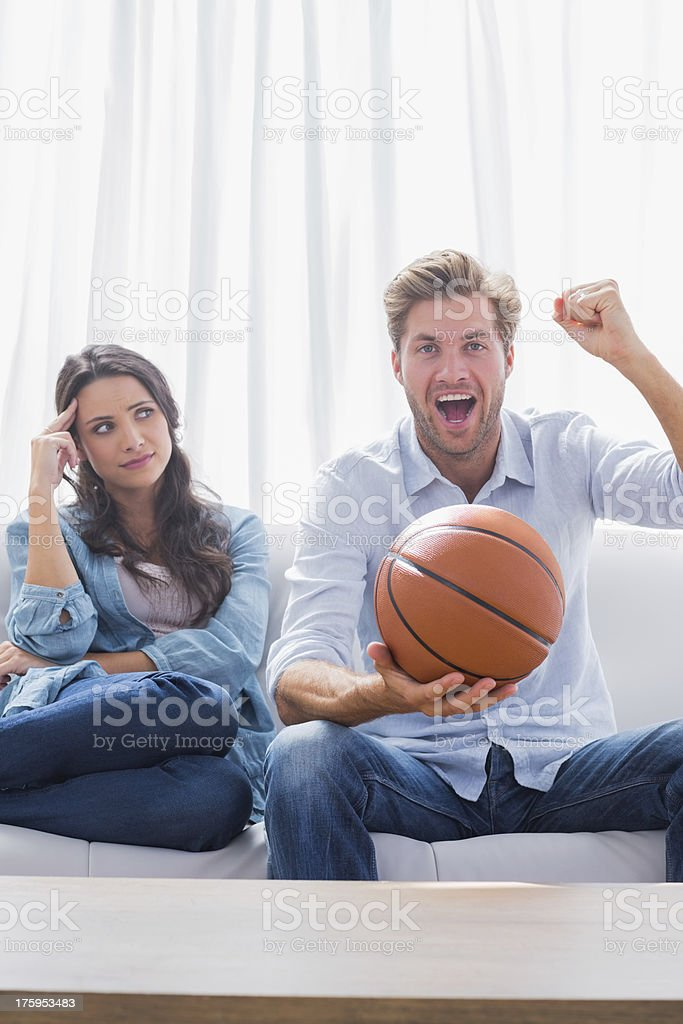 Woman looking at her husband cheering the basketball game stock photo