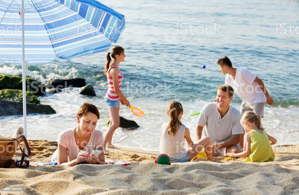 Woman looking at her mobile phone while her family  playing on beach stock photo
