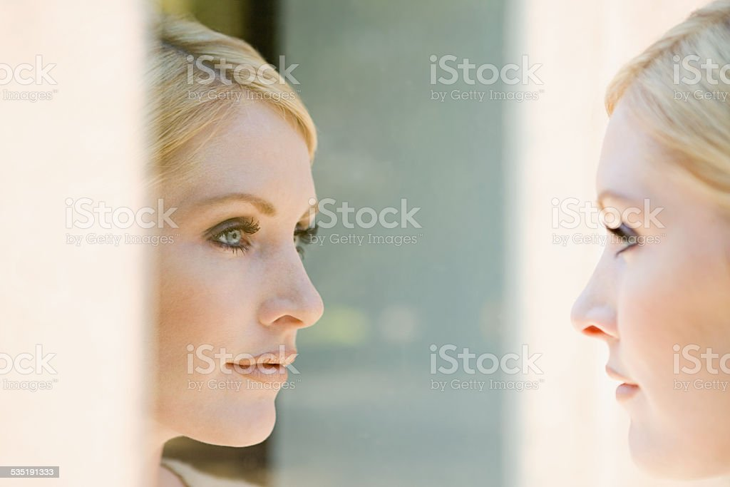 Woman looking at her reflection stock photo