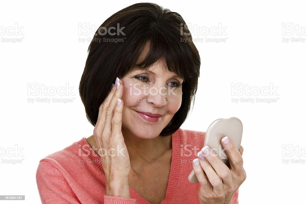 Woman looking at her skin in mirror royalty-free stock photo
