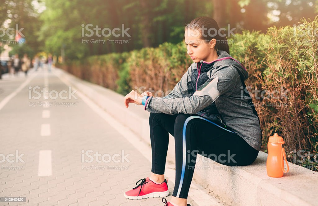 Woman looking at her sport watch stock photo