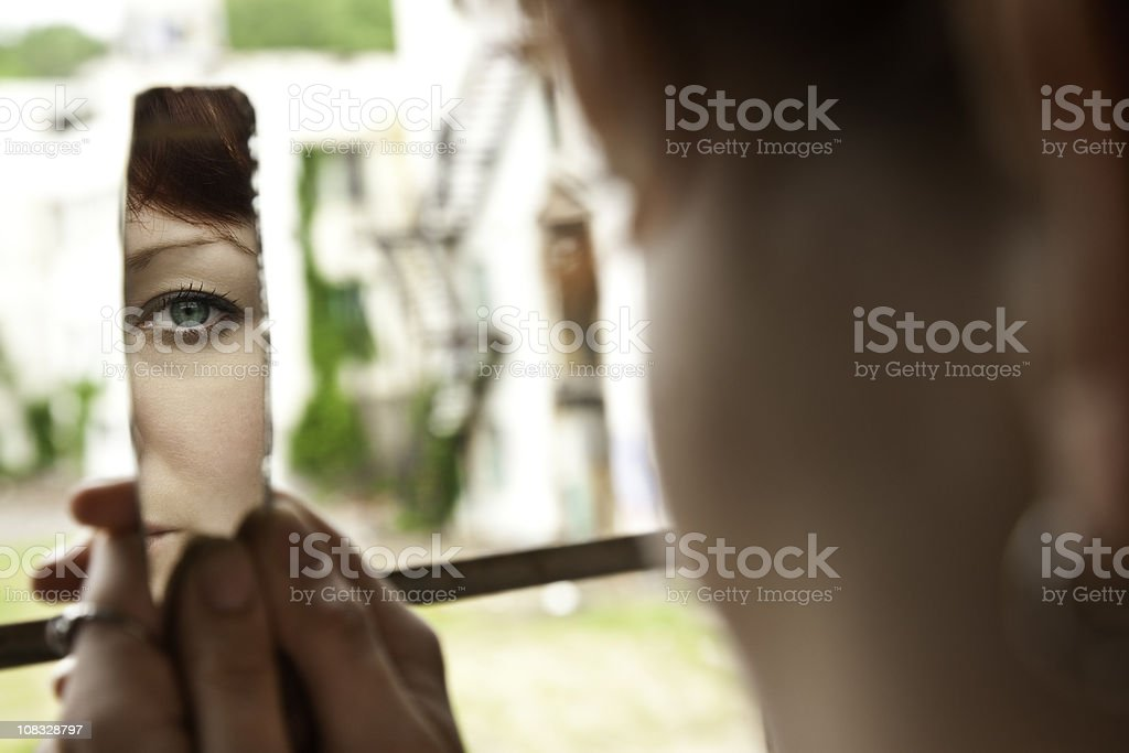 Woman Looking at Herself in a broken mirror royalty-free stock photo