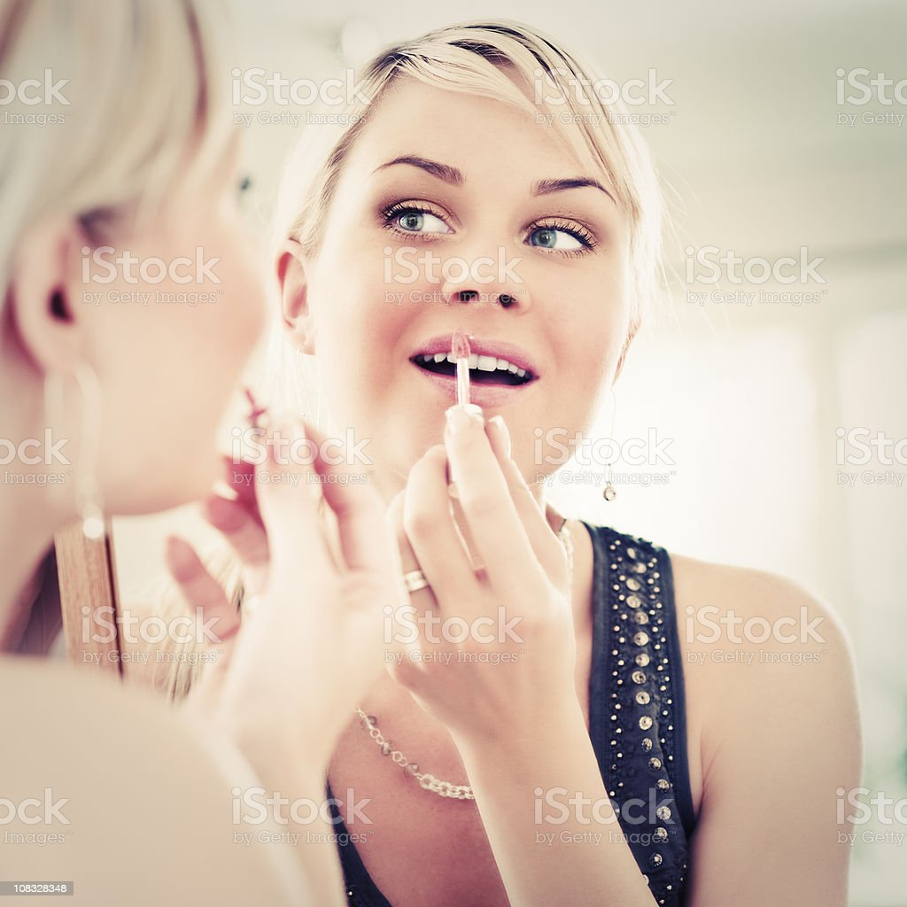 Woman looking at herself in a mirror applying lip gloss royalty-free stock photo