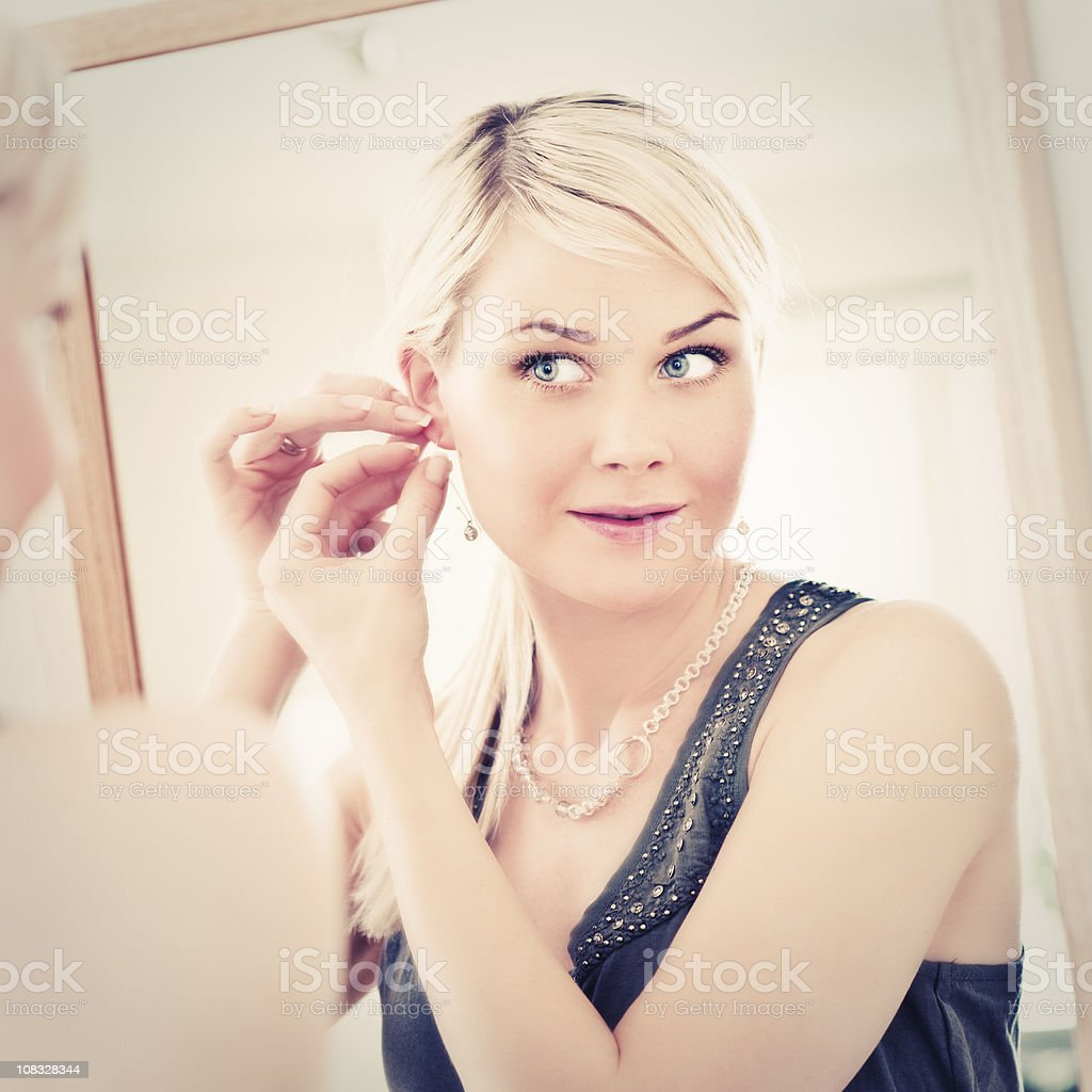 Woman looking at herself in a mirror trying on earrings royalty-free stock photo