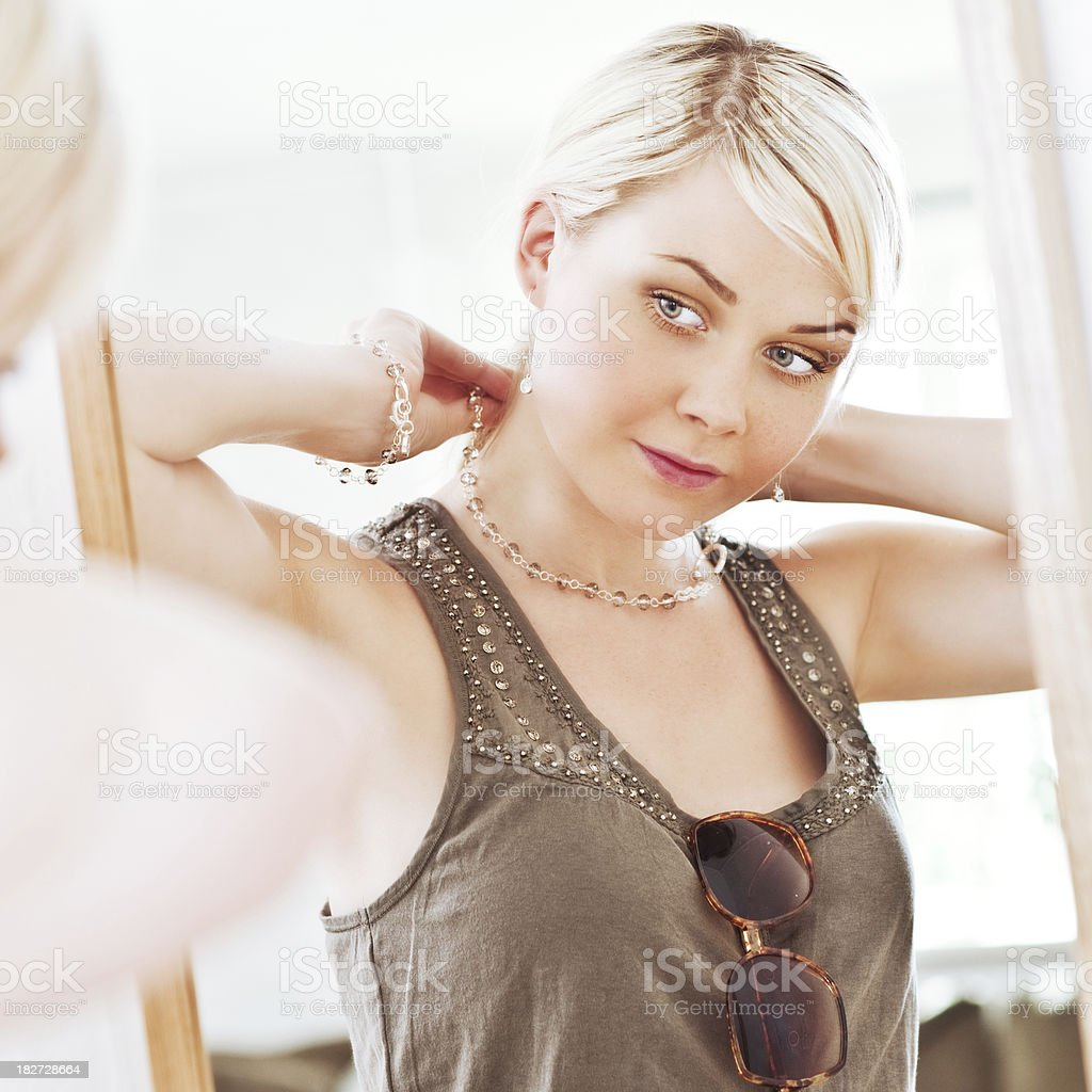 Woman looking at herself in a mirror trying on necklace royalty-free stock photo