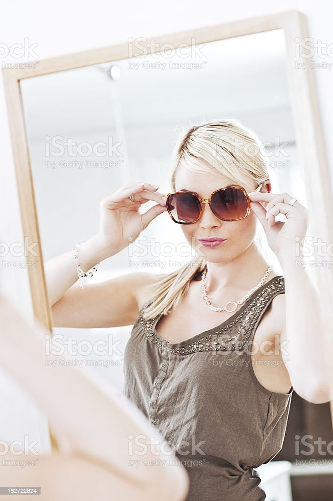 Woman looking at herself in a mirror with sunglasses royalty-free stock photo
