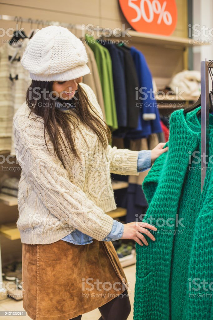 Woman looking at knitted green cardigan in store stock photo