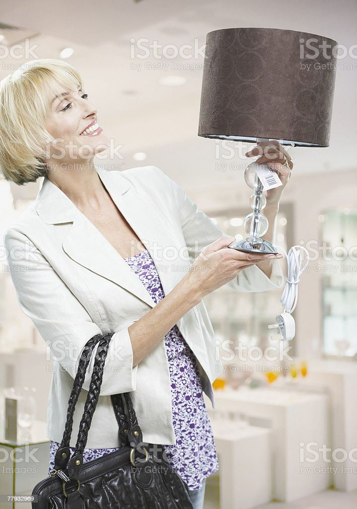 Woman looking at lamp in store royalty-free stock photo