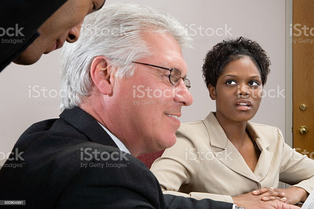 Woman looking at men whispering stock photo