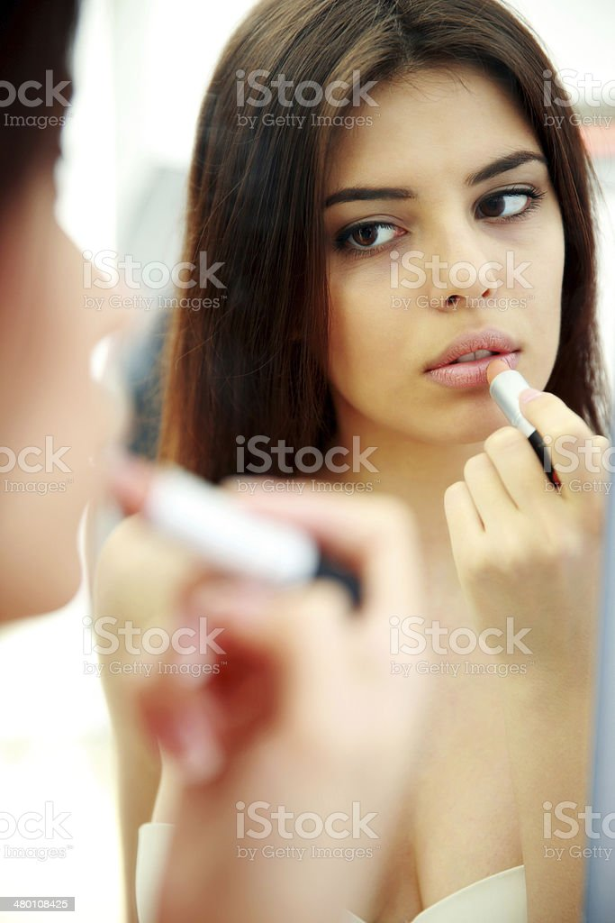 woman looking at mirror while doing makeup royalty-free stock photo