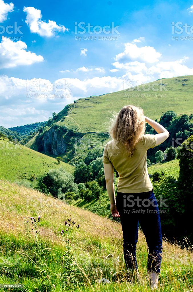 Woman looking at mountainous landscape in English Peak district stock photo