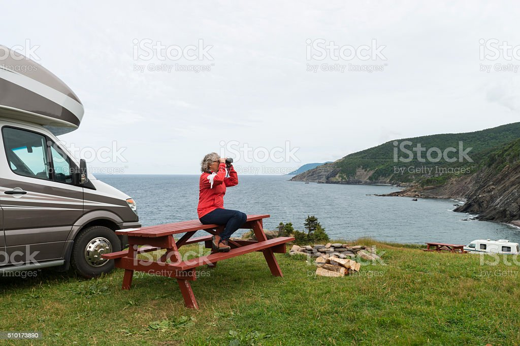 Woman looking at nature with binoculars stock photo