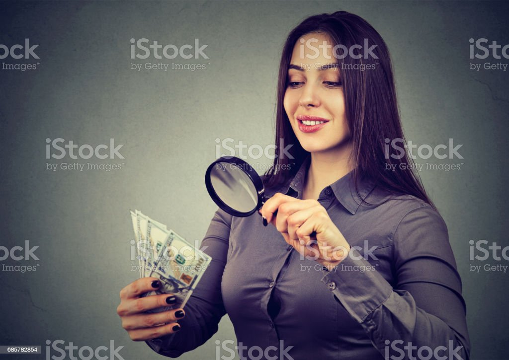 woman looking at one hundred dollar bills through magnifying glass stock photo