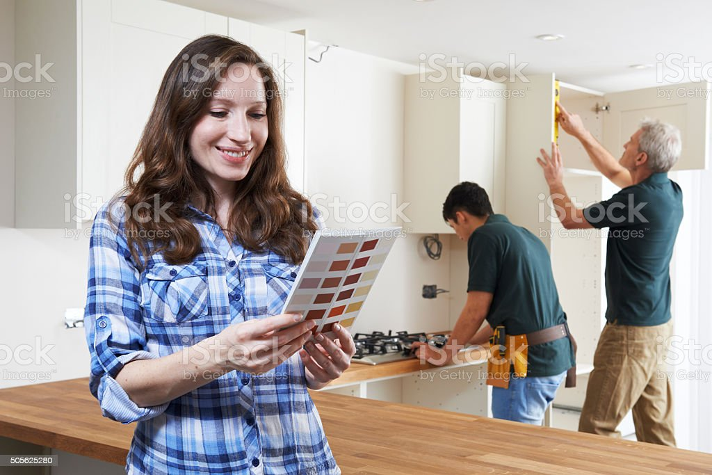 Woman Looking At Paint Chart In New Kitchen stock photo