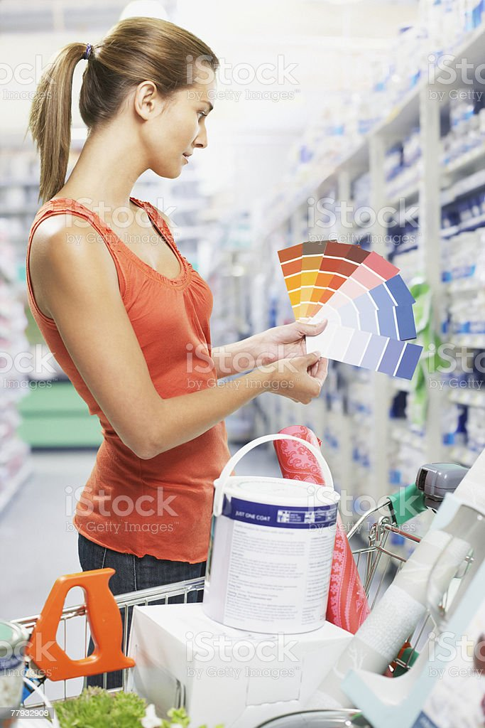 Woman looking at paint samples in store stock photo