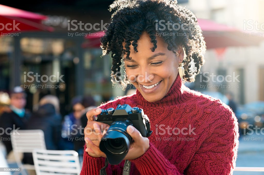 Woman looking at pictures in camera stock photo