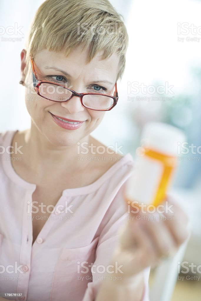 Woman Looking At Pill Bottle stock photo
