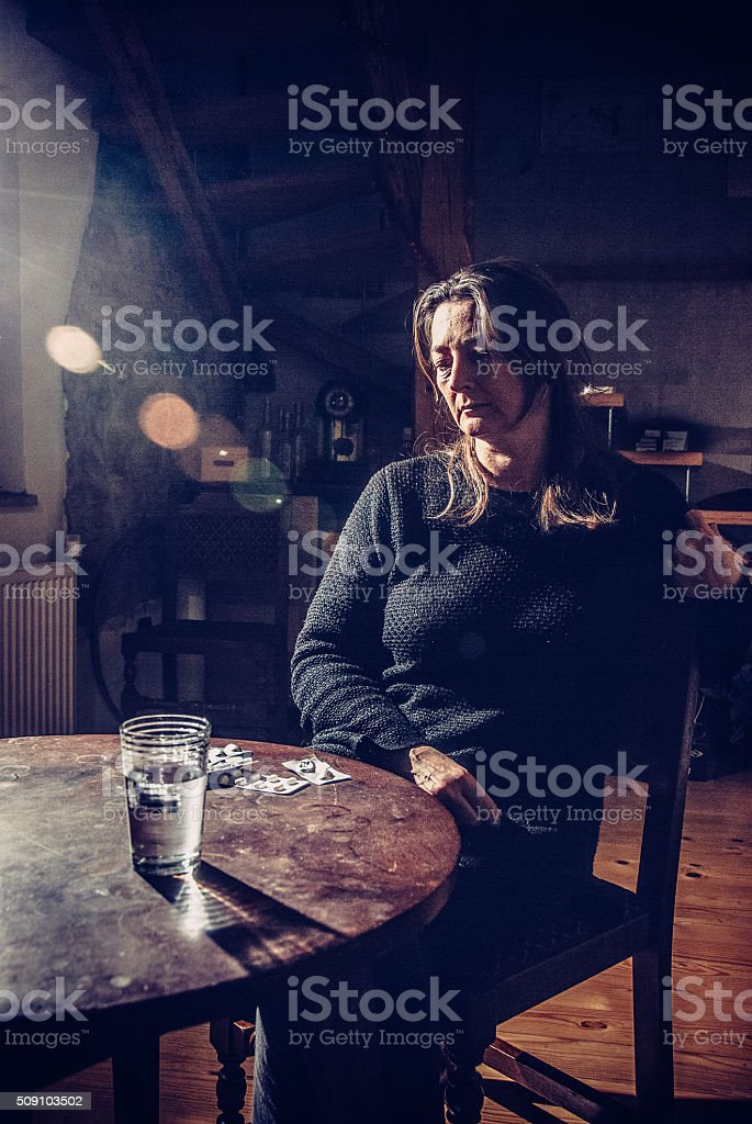Woman Looking at Pills on the Table stock photo