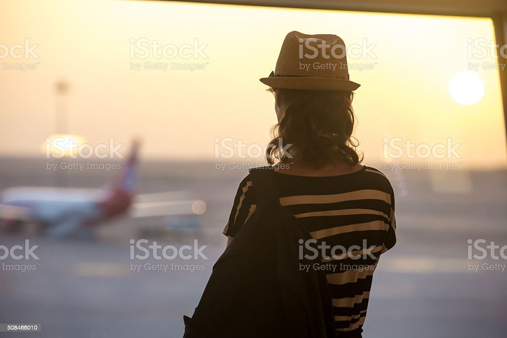 Woman looking at planes, back view stock photo
