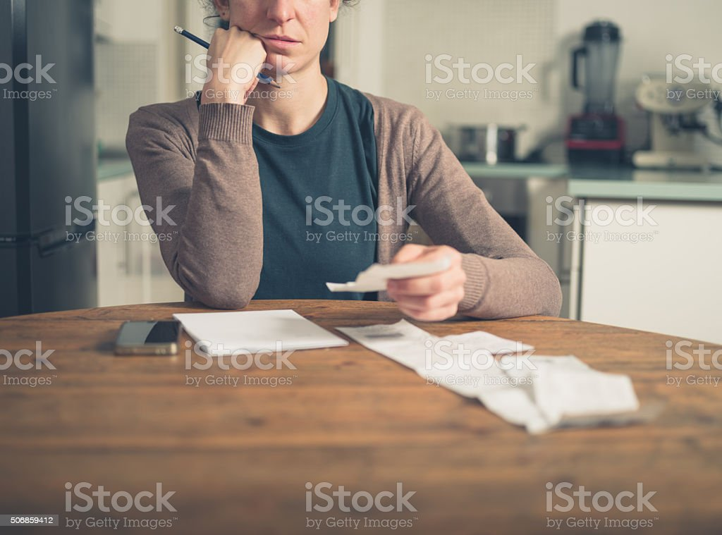 Woman looking at receipts at home stock photo