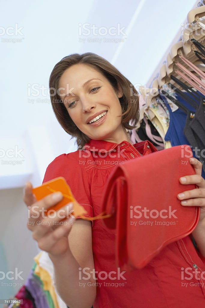 Woman looking at sales tag on purse royalty-free stock photo