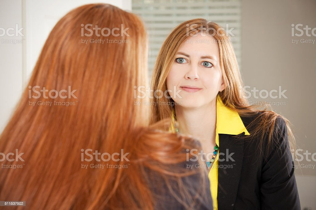 Woman Looking At Self In Mirror stock photo