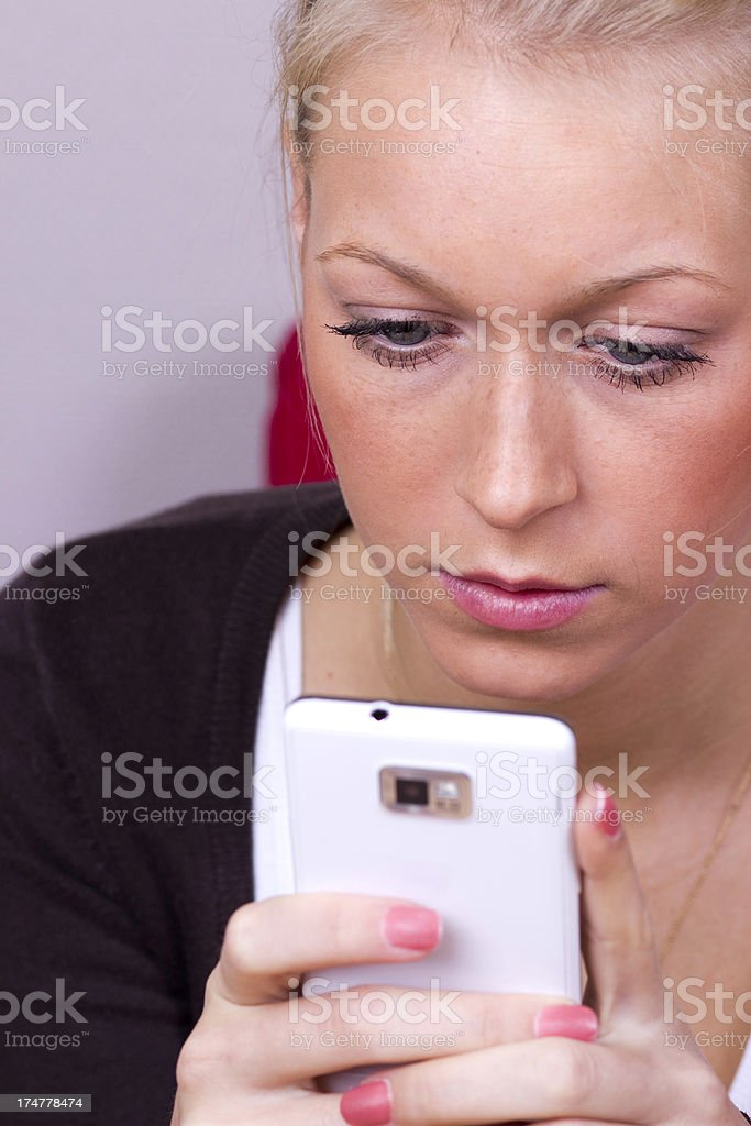 Woman looking at smartphone headshot royalty-free stock photo