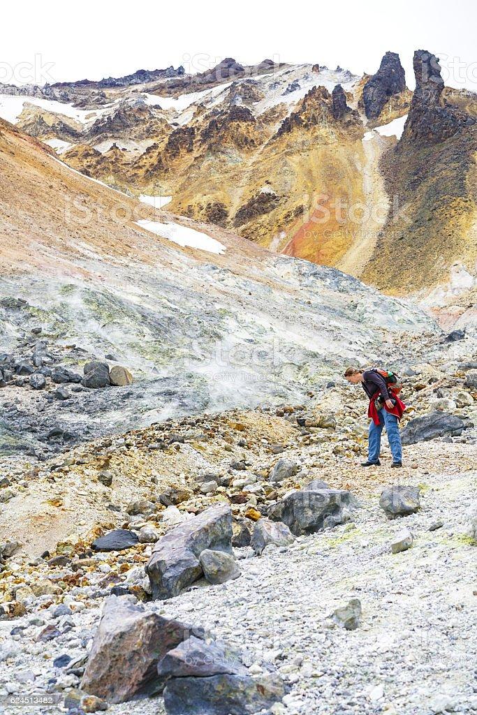 Woman looking at smoking ground of Tokachidake volcano crater, Hokkaido stock photo