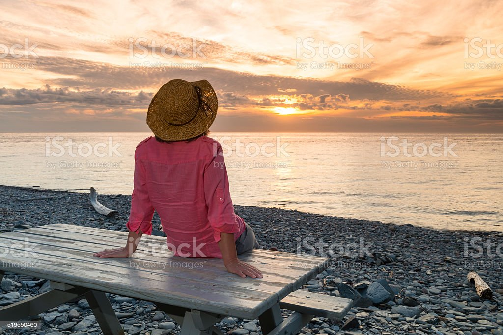 Woman looking at sunset, sitting on picnic table stock photo