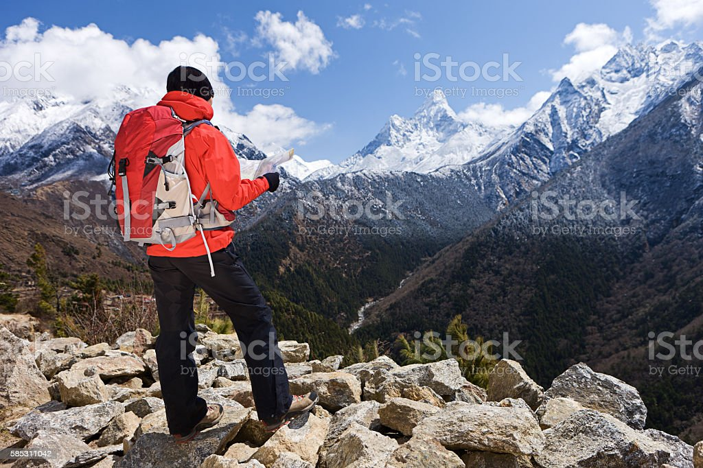 Woman looking at the map in Himalayas, Nepal stock photo