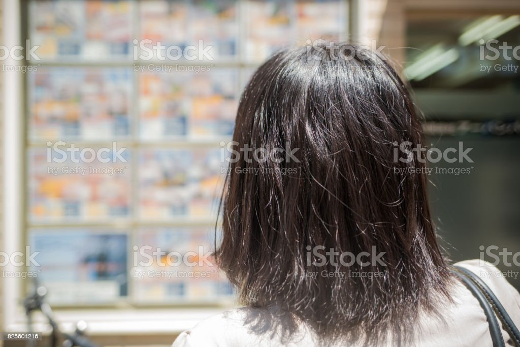Woman looking at the real estate sign stock photo