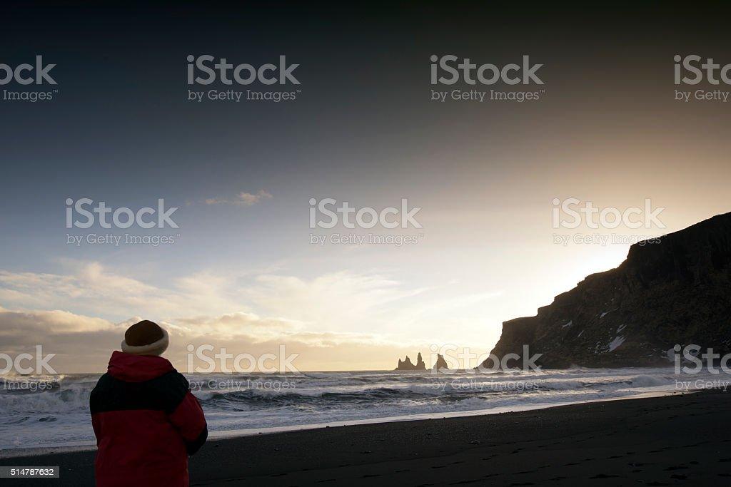 Woman  looking at the Reynisdrangar basalt sea stacks , Vik,Iceland stock photo