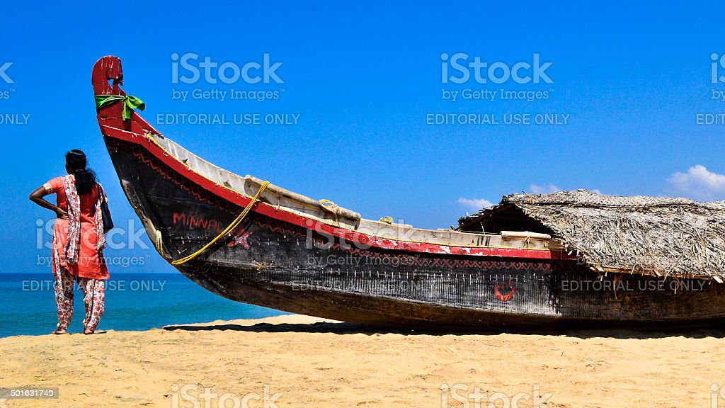 Woman looking at the sea next to a boat stock photo
