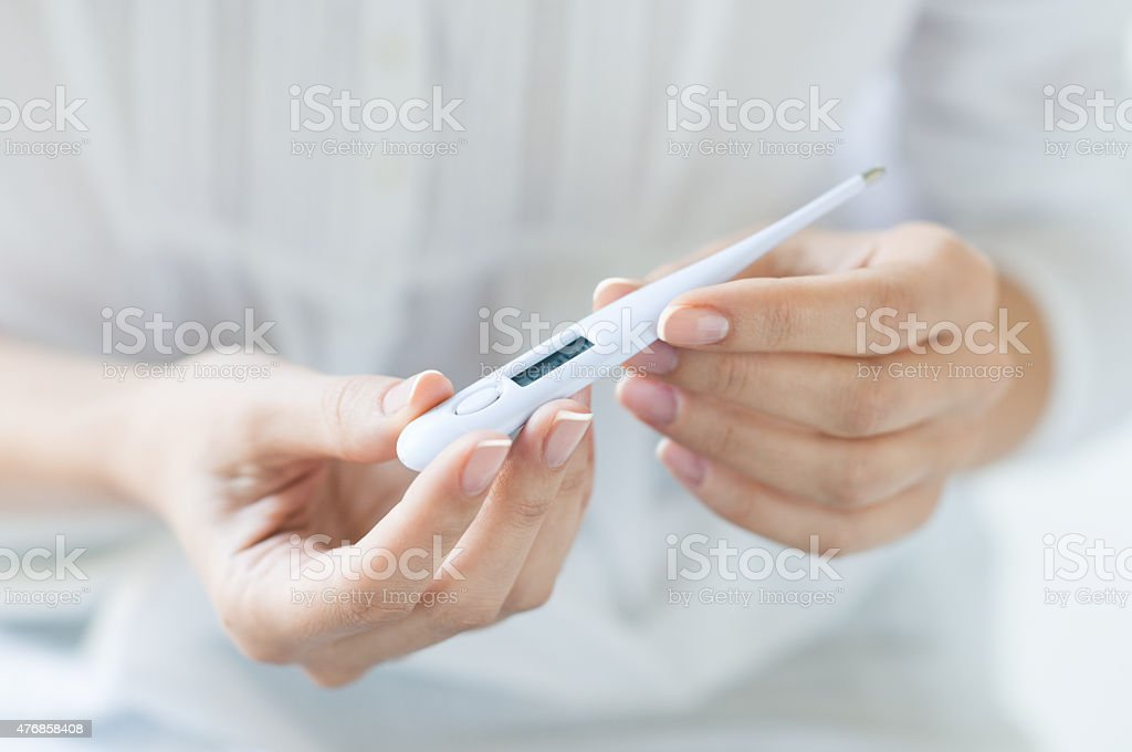 Woman looking at thermometer stock photo