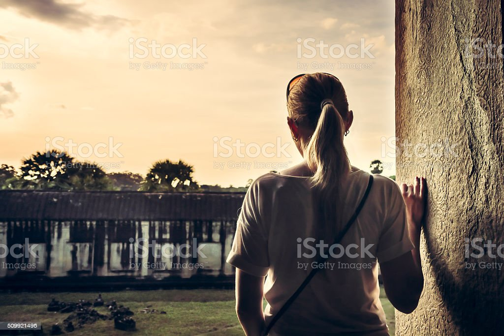 Woman looking at view during sunset through ancient window stock photo