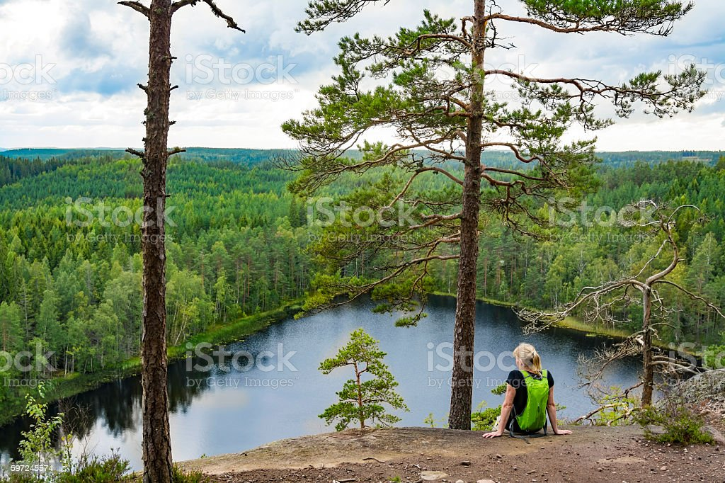 Woman looking at view on high cliff stock photo