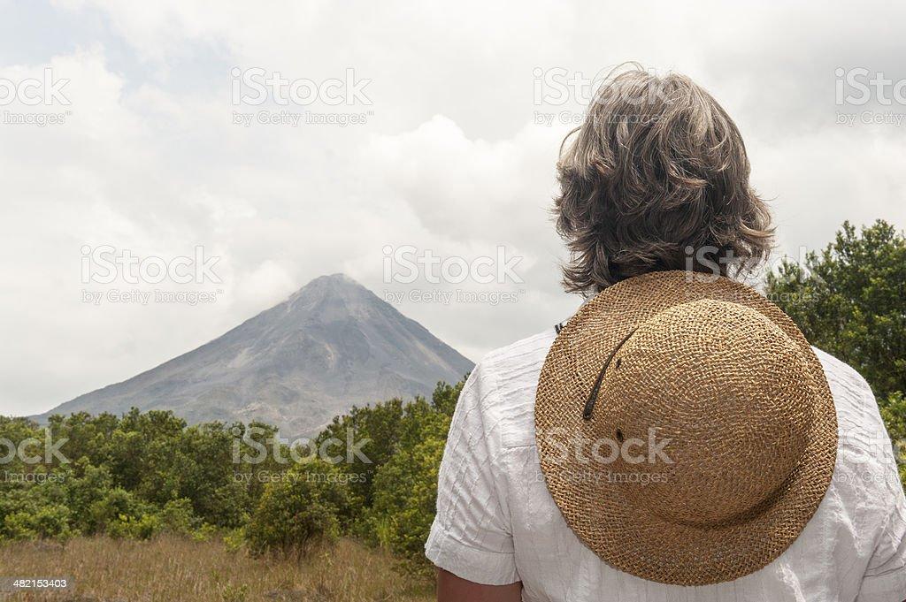Woman looking at volcano stock photo