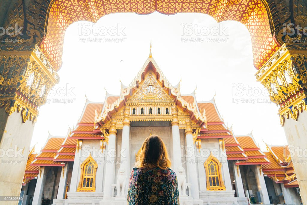 Woman looking at Wat Pho temple at sunrise stock photo