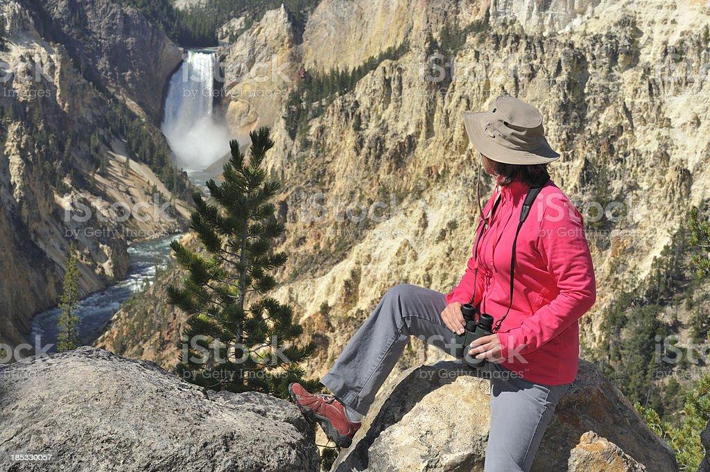Woman looking at waterfall, Yellowstone stock photo