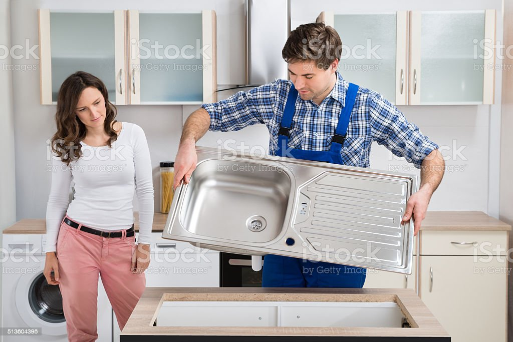 Woman Looking At Worker Carrying Kitchen Sink stock photo