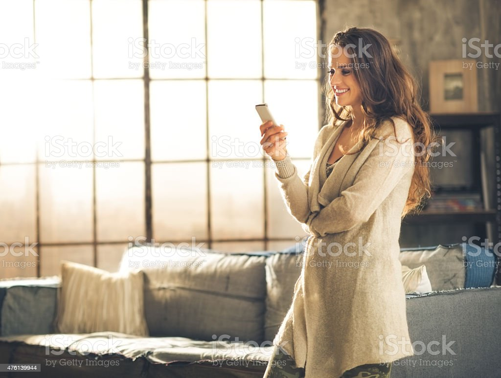 Woman looking away holding phone standing in loft apartment stock photo