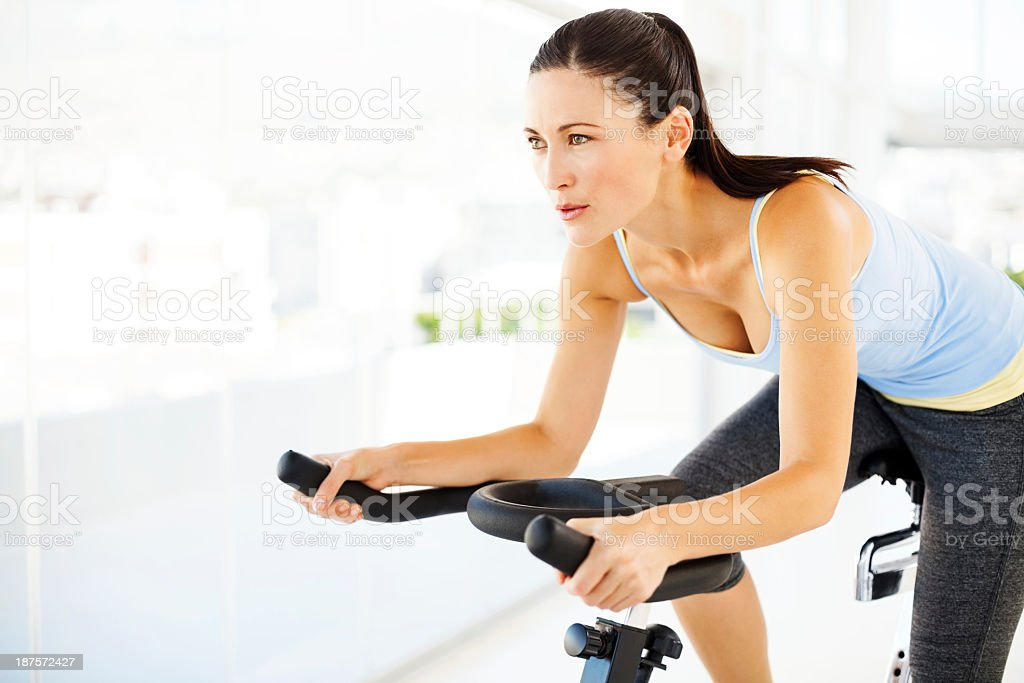 Woman Looking Away While Exercising On Bike In Gym stock photo