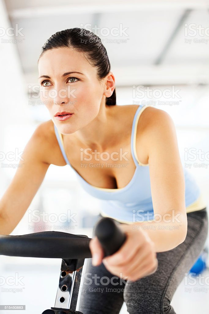 Woman Looking Away While Spinning On Exercise Bike In Club stock photo