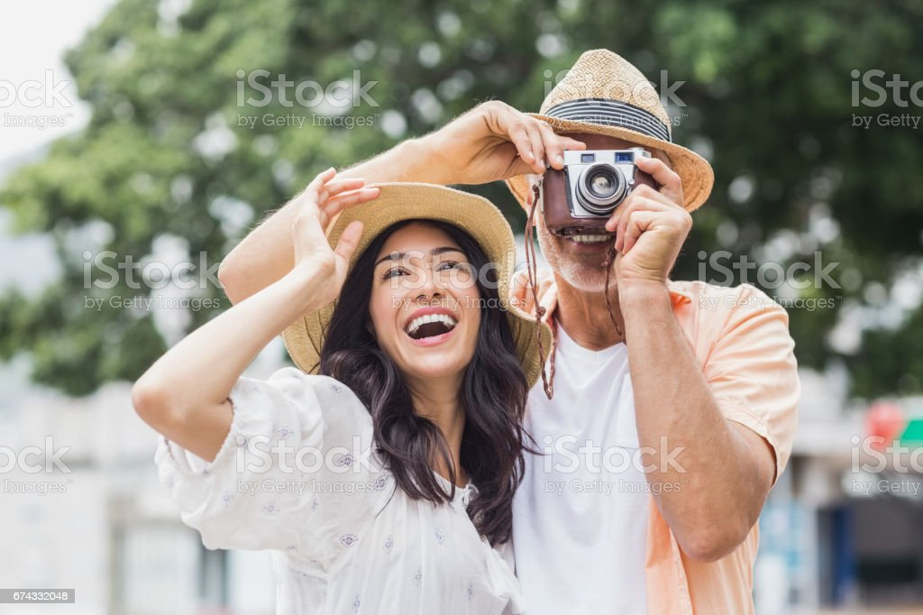 Woman looking away while man photographing stock photo