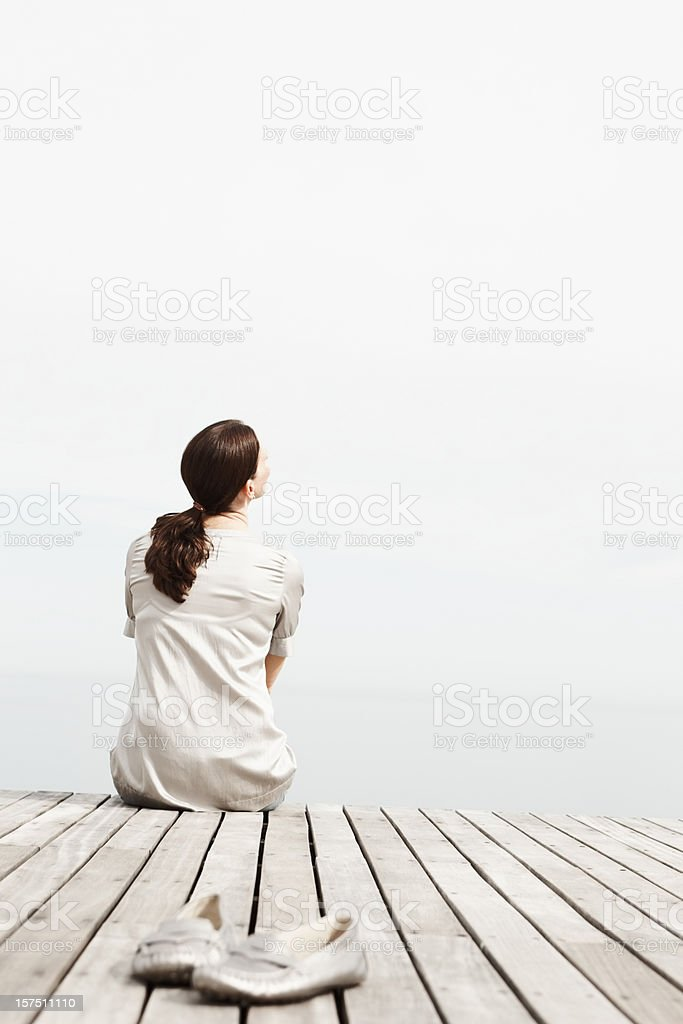 Woman looking away while sitting on a pier royalty-free stock photo