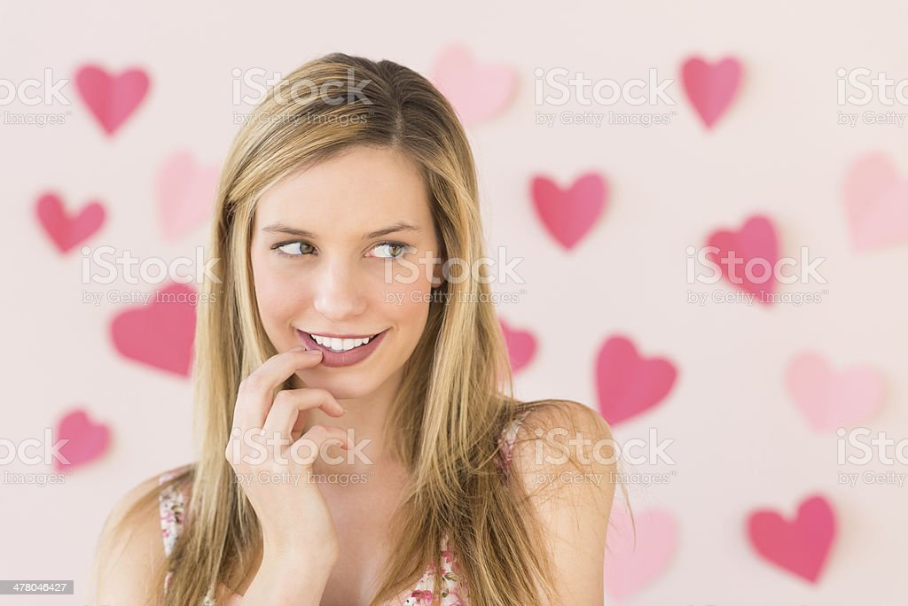 Woman Looking Away With Heart Shaped Papers Against Pink Backgro royalty-free stock photo
