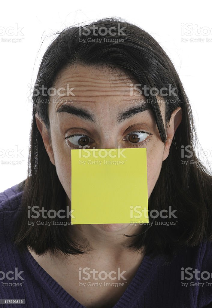 Woman Looking Cross-Eyed at Blank Sticky Note on her Nose royalty-free stock photo