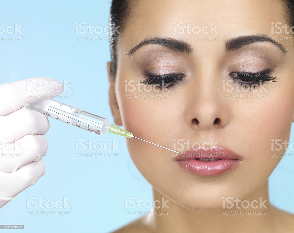 Woman looking down as medical professional injects face royalty-free stock photo