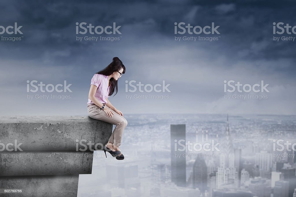 Woman looking down from the rooftop stock photo