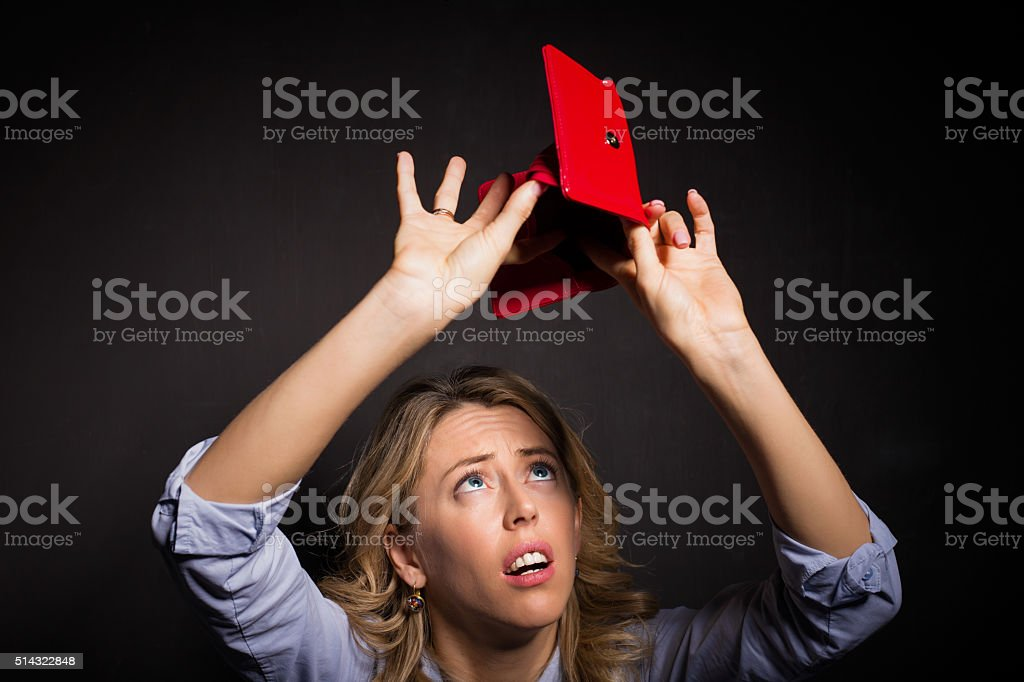 Woman looking for money in her wallet stock photo